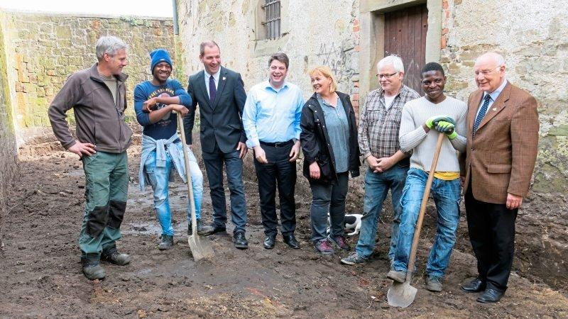 Es geht voran mit der Sanierung und dem Umbau des alten Gefängnisses in Fürstenau. Darüber freuen sich Ralf Heitkamp, Benno Trütken, Christian Calderone, Heike Holten, Werner Pries und Herbert Gans sowie Helfer aus den Reihen der Flüchtlinge.