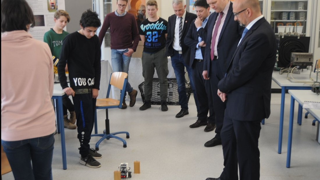 Stoppt das Auto oder nicht? Ein Schüler erklärt Minister Björn Thümler (2. von rechts), wie man ein Fahrzeug mit Hilfe einer App auf autonomes Fahren trimmt.